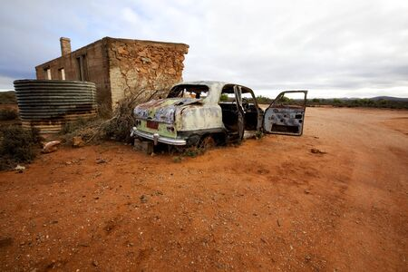 wrecked: Wrecked abandoned car alongside remains of ruined 19th century stone house.  Silverton, outback New South Wales, Australia. Stock Photo