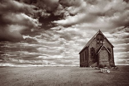 monotone: Abandoned church in the desert, with stormy skies.  Monotone image, with added grain.