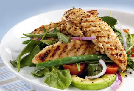 arugula: Salad of grilled chicken tenderloins with avocado, tomatoes, red onion, green beans, spinach and arugula. Delicious healthy eating. Stock Photo