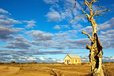 broken hill: Abandoned church in the desert, in sunset light.  Dead tree in foreground.  Silverton, New South Wales, Australia. Stock Photo