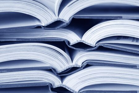 Open text books in a pile, in blue tone. photo
