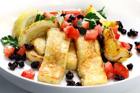 haloumi: Grilled haloumi cheese with a salad of tomatoes, currants and parsley.  With grilled lemon wedges.  Popular in Greece, Cyprus, Turkey, and the Middle East.