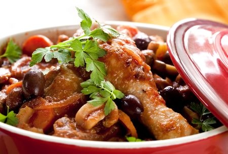 Chicken cacciatore in a red crock pot, ready to serve.  Shallow DOF.