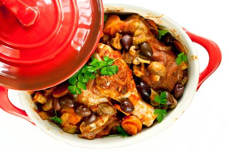 crock: Chicken cacciatore in a red crock pot, ready to serve.  Overhead view, over white background. Stock Photo
