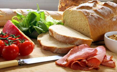 cherry tomatoes: Preparing a sandwich, with fresh-sliced bread, cherry tomatoes, pastrami, cheese, lettuce,, and mustard, on chopping board.