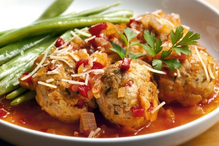 parmesan: Chicken meatballs with green runner beans.  Simmered in a rich herbed tomato sauce, and topped with parmesan and parsley. Stock Photo