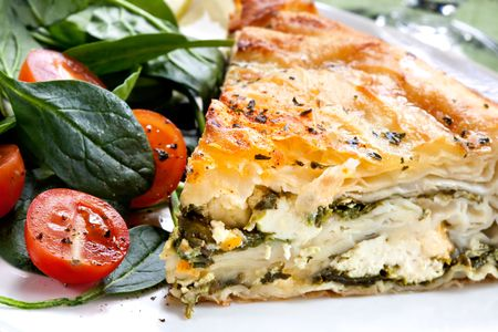 Delicious spinach and feta cheese pie, with filo pastry.  Traditional Greek spanakopita, with salad. photo