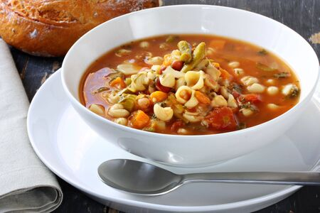 minestrone: Bowl of minestrone pasta soup, on rustic table, with cob of tomato bread.