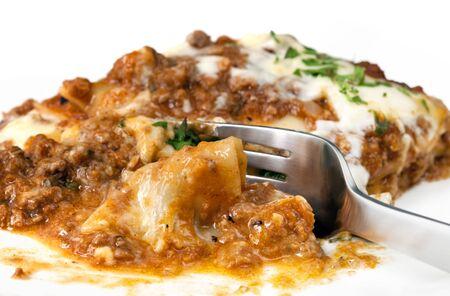 cutting through: Close-up of a fork cutting through hot lasagne. Stock Photo
