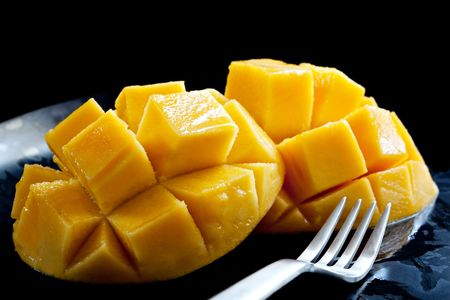Luscious cut mango on a black plate with fork, ready to eat. Imagens