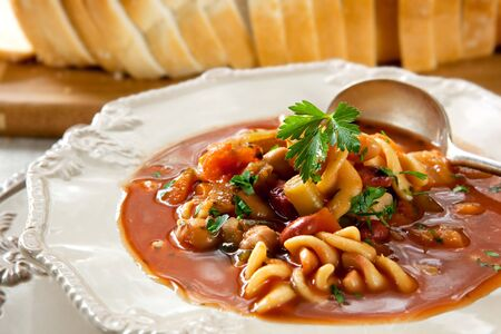 Bowl of minestrone pasta soup, hearty and delicious, with bread. photo