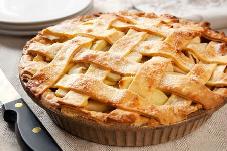 apple pie: Home-baked lattice apple pie, in a brown ceramic pie plate, ready to serve. Stock Photo