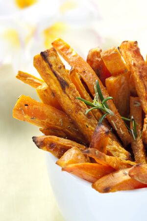 papas fritas: Papas fritas de camote con romero, al horno listo para picar. Poca profundidad de campo. Foto de archivo