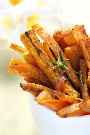 s��kartoffel: Sweet Pommes frites mit Rosmarin, �berbacken bereit f�r Zwischenmahlzeiten. Shallow depth of field.