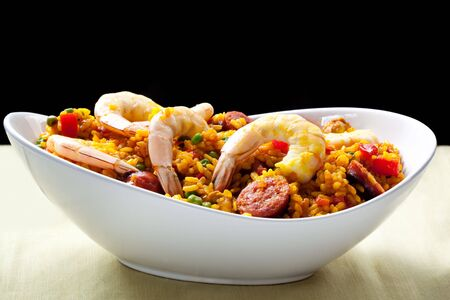 chorizo: Paella with prawns, chorizo, tomatoes, peppers and peas, in a white serving bowl.