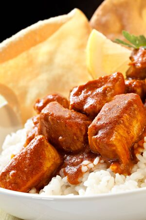 Butter chicken over rice, with pappadoms.  Delicious Indian food. photo