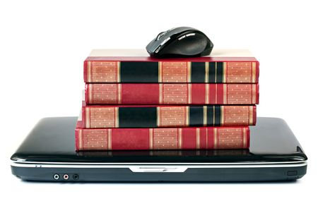 Reference books stacked on top of a laptop, with mouse.  On-line learning concept.  Isolated on white. photo