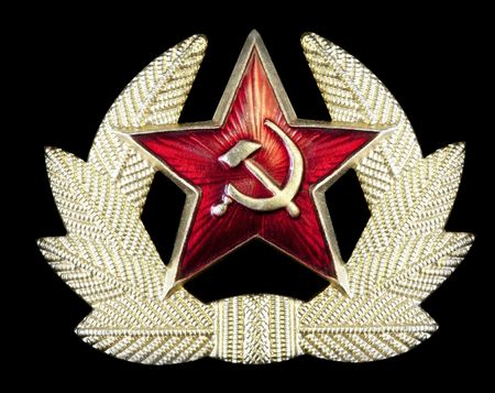 Pin badge with Russian hammer and sickle in a star-shape, surrounded by golden feathers.  Isolated on black. photo