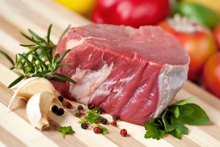 Thick-cut fillet steak, ready for cooking, on a board with garlic, peppercorns and herbs. photo