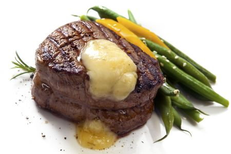Thick-cut fillet steak with Bearnaise sauce, accompanied by green beans and yellow capsicum.