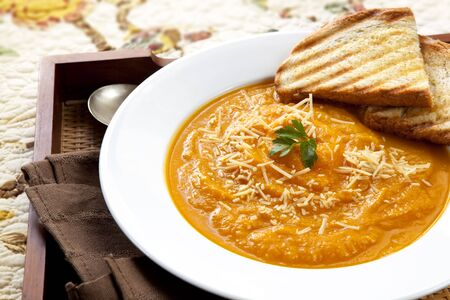 serving tray: Pumpkin soup with parmesan cheese and crusty toasted bread, on a serving tray.