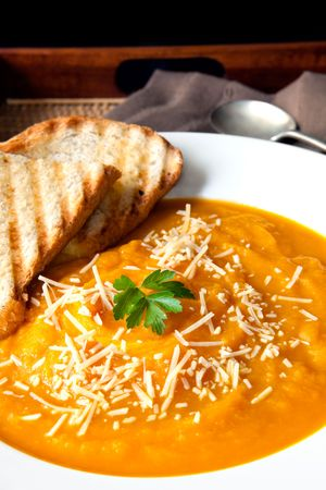 Pumpkin soup with parmesan cheese and crusty toasted bread, on a serving tray. photo