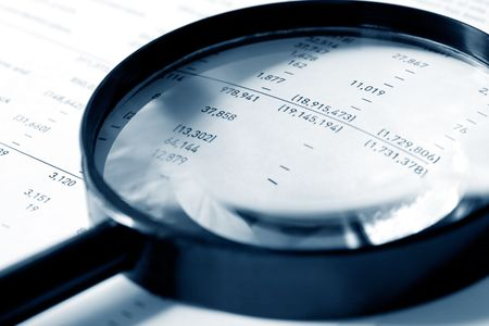 Magnifying glass over financial figures.  Shallow DOF, cyan tone. photo