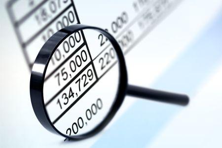 auditor�a: Lupa sobre las cifras financieras.  Enfoque muy suave. Foto de archivo