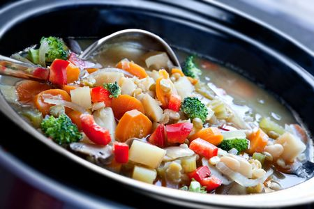 crock pot: Vegetable soup, slow-cooked in a crock pot, ready to serve. Stock Photo