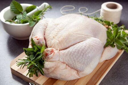roasted chicken: Raw chicken on a board, with fresh herbs, and trussed ready for roasting.