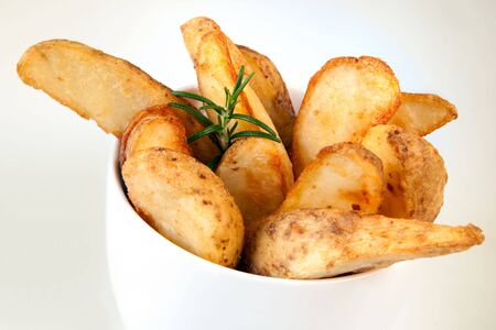 fries: Potato wedges, straight from the oven, ready to eat, in a white bowl. Stock Photo