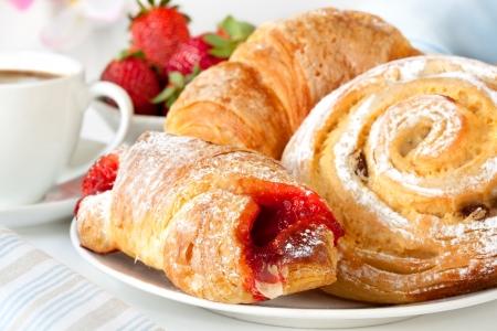 Continental Frühstück mit Auswahl an Gebäck, Kaffee und frischen Erdbeeren.