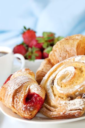 french bread rolls: Continental breakfast with assortment of pastries, coffees and fresh strawberries.
