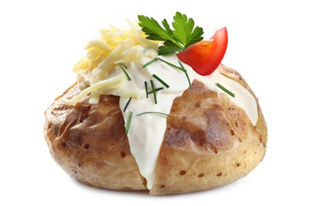 Baked potato filled with sour cream, grated cheese, and tomato.  Garnished with chives and parsley, isolated on white.