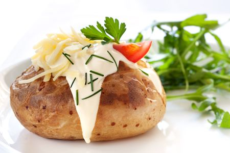 Baked potato filled with sour cream and grated cheese, with arugula on the side.