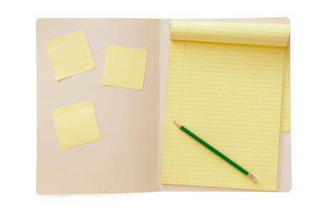 carpetas: Carpeta abierto de manila, con el Bloc de notas con l�neas amarilla y l�piz y notas adhesivas.  Foto de archivo
