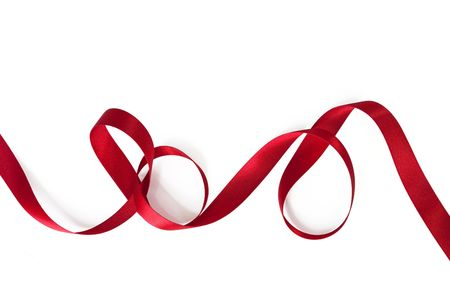 Red satin ribbon, curling over white background. photo