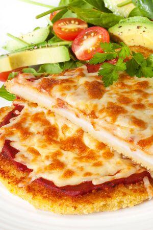 carne de pollo: Escalope de pollo cubiertas de queso y pur� de fusi�n, con espinaca, aguacate, ensalada de tomate. Foto de archivo