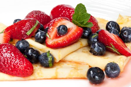 Crepes with strawberries and blueberries, garnished with mint.  Delicious eating!