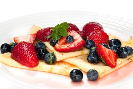 Crepes with strawberries and blueberries, garnished with mint.  Delicious eating! photo