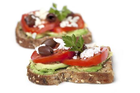 Wholegrain toast with avocado, tomato, feta cheese and black olives.  Delicious healthy snacking. photo