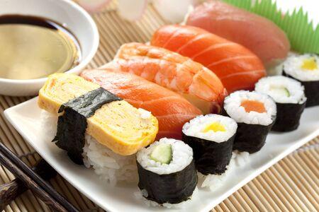 寿司醤油とお箸、竹の背景の上のプレート。