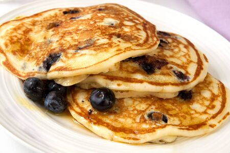angled view: Buttermilk pancakes with blueberries and maple syrup.  A sweet treat.