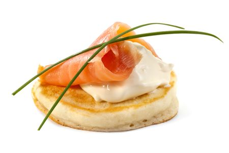blini: Blini with smoked salmon and sour cream, garnished with chives.  Close-up view, isolated on white.