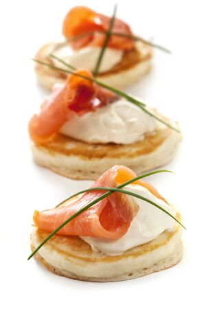 smoked salmon: Blinis with smoked salmon and sour cream, garnished with chives.