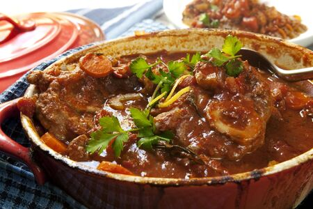 Delicious veal shanks, slow-cooked with vegetables, in a red crock pot.  Traditional osso buco. photo
