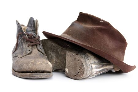 recently: Battered old workboots and felt hat, isolated on white.  Well used from the 1940s until recently.