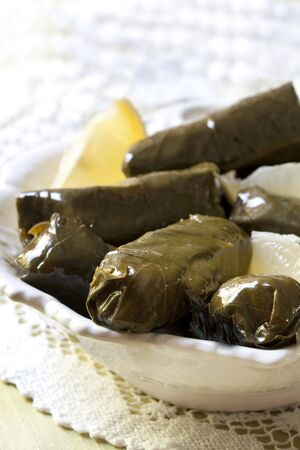 wedges: Dolmades with lemon wedges.  Traditional Greek stuffed vine leaves.