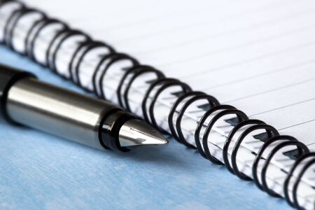 fountain pen on open spiral notebook.  Shallow depth of field, with focus on pen tip. photo