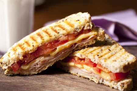 ham sandwich: Grilled sandwich with ham, cheese and tomato, and a glass of milk behind.